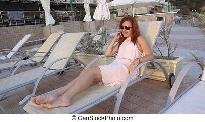 girl at the resort by the sea and the pool talking on the phone