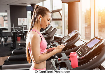 girl at the running track with a phone
