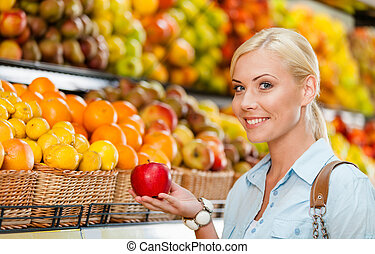 Girl at the shop choosing fruits hands apple