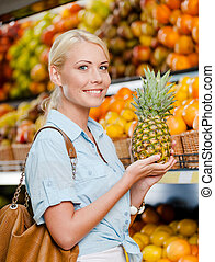 Girl at the shop choosing fruits hands pineapple