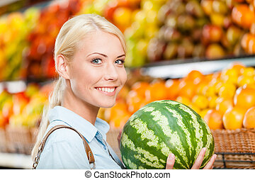 Girl at the shop choosing fruits hands watermelon
