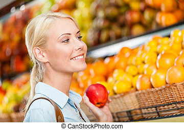 Girl at the store choosing fruits hands apple