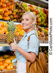 Girl at the store choosing fruits hands pineapple
