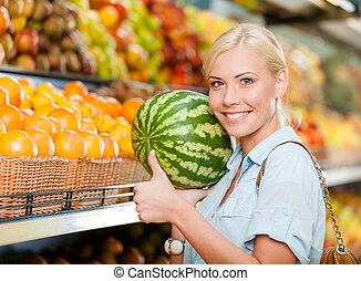 Girl at the store choosing fruits hands watermelon