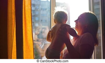 girl at the window playing with a child in the sun
