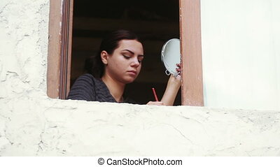 Girl at window does makeup