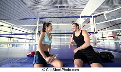 Girl athlete and fitness instructor talking and smiling to each other