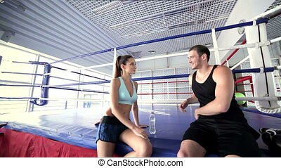 Young and successful boxing coach welcomes female athlete in the classroom for boxing in the ring. Sexy young girl doing a athletic exercise and meets his instructor.