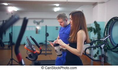 girl athlete drinking water get tired in gym trainers sport...