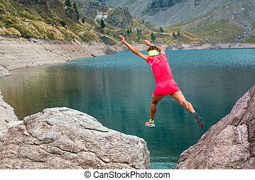 Girl athlete jumps between its stones in the mountains