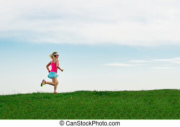 Girl athlete runs in the meadow