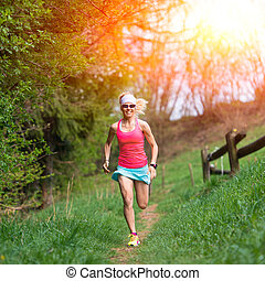 Girl athlete runs into the forest and meadow
