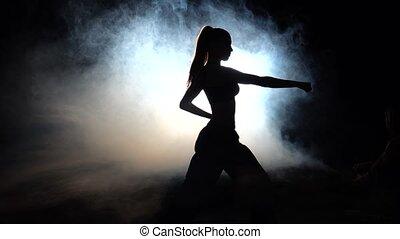 Girl athlete shows power moves. Black. Silhouette. Backlight...
