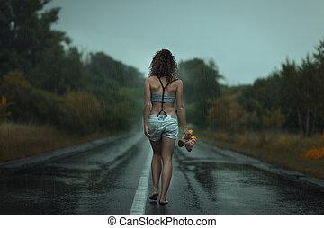 Girl back. Walks on the road. Under rain.