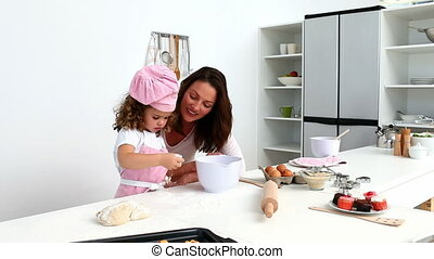 Girl baking biscuits with her mother in the kitchen