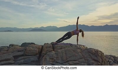 Girl Balances on Right Arm in Yoga Pose on Beach at Dawn