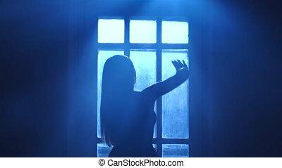 Girl ballerina kneads and dances near window in moonlight,...
