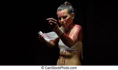 Girl bandaging wounds - Footage of bandaging woman on black...