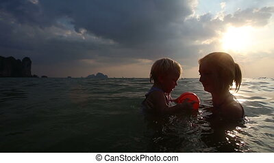 girl bathed with mother in the sea at sunset