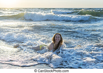 Girl bathes in waves of the sea