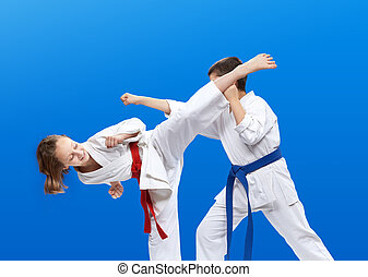 Girl beats kicking  boy is beating hand on the blue background