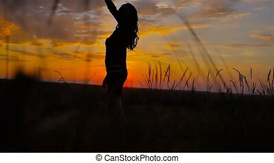 girl beautiful her arms standing in a field at sunset slow motion video