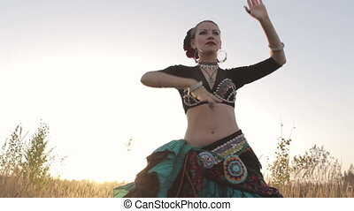 Girl beautifully dancing belly dance on the nature