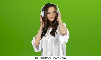 Girl begins to dance, she is in a good mood. Green screen