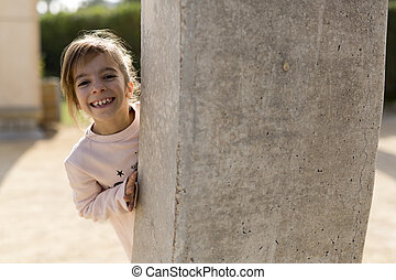 Girl behind a stone wall.