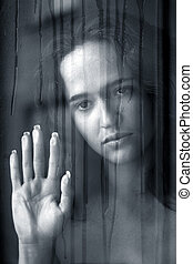 Girl behind glass - woman with sad smile behind a wet window