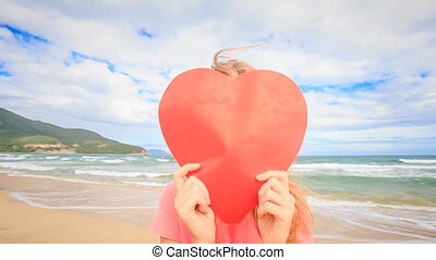Girl behind Large Red Heart Guy Appears Kisses on Beach