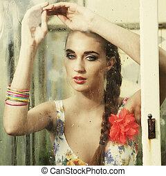 girl behind wet window