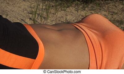 girl belly makes ABS exercises outdoors - close-up of a girl...