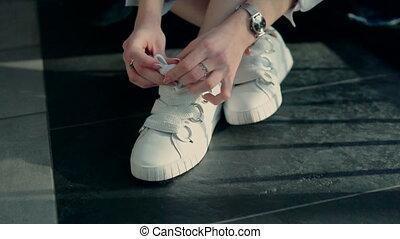 Girl Binding Laces - Young stylish girl sitting on the floor...