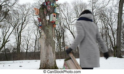 girl bird nest house hang - careful woman in grey coat carry...