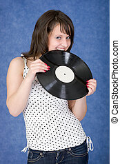 Girl biting a phonograph record on a blue background