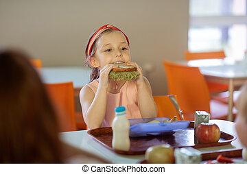 Beautiful dark-eyed girl biting her sandwich with lettuce
