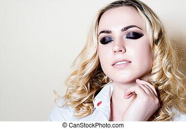 Girl blonde eye make-up on a light background