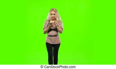 Girl blonde goes and look at your phone. Green screen