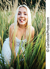 Girl blonde sitting in grass shows tongue fun.