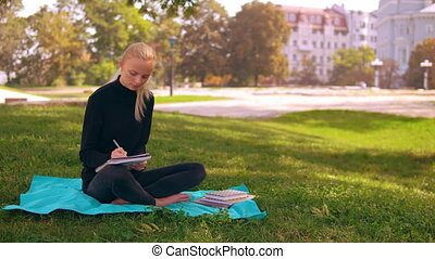 girl blonde writing in notebook outdoors - young caucasian...