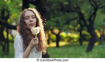 Girl Blow on a Dandelion - Woman blowing dandelion seeds at...