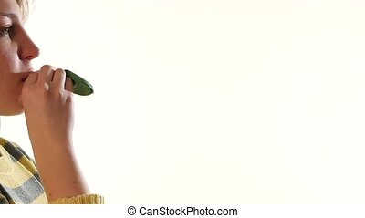 Girl blowing a green balloon isolated on white background, slow motion