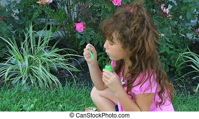 Girl Blowing Bubbles - Little girl blowing bubbles and...
