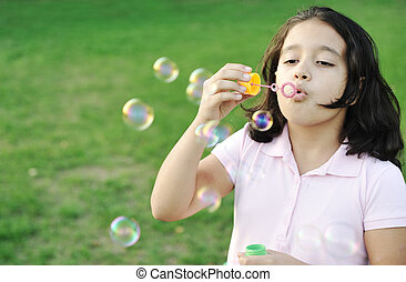 Girl blowing bubbles outdoor