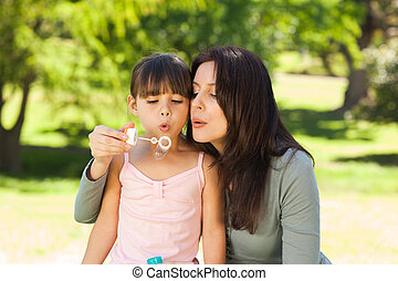 Girl blowing bubbles with her mother in the park