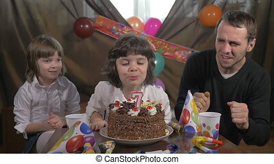 Girl blowing candles with family