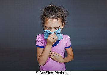 girl blowing his nose into a handkerchief on gray background