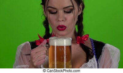 Girl blowing in glasses with beer and squirting it into her...