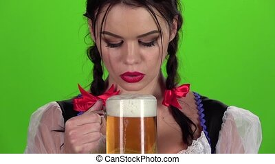 Girl blowing in glasses with beer bites his lip. Slow motion...